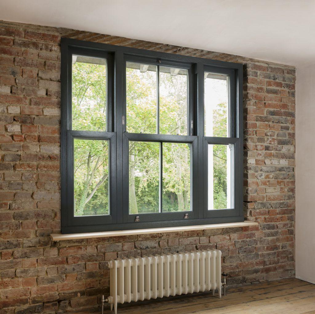 Black wood sash windows in red brick building.