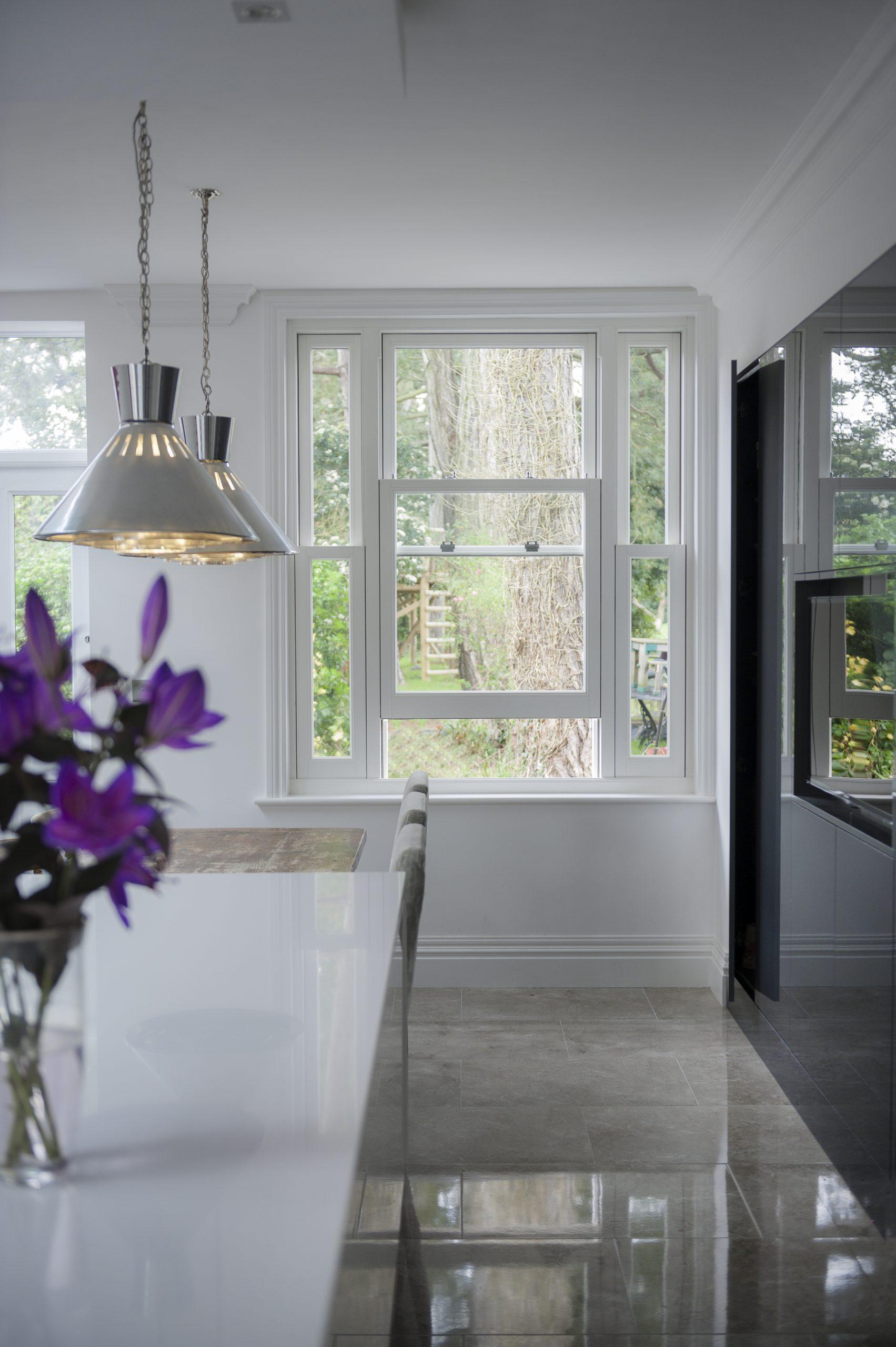 Slightly open white sash window in kitchen.